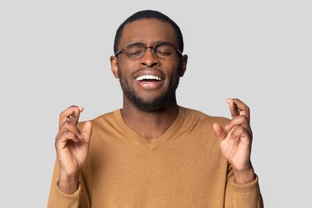 Hopeful superstitious millennial african american guy crossing fingers, wishing good luck head shot close up portrait. Excited smiling black man waiting for entrance exams or job interview results.