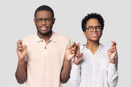 Superstitious young african american family spouse standing together, crossing fingers, hoping for getting bank credit or mortgage, wishing good luck, goal achievement, isolated on grey background. Foto de archivo