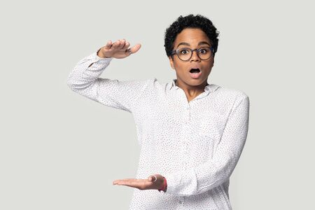 Surprised millennial african american woman in eyeglasses showing big measurement, isolated on gray studio background. Amazed ethnic girl banging eyes, demonstrating something huge, discount concept.