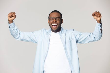 Hilarious excited african american young man celebrating success, favorite sport team win. Lucky black male successful winner motivated by goal achievement, isolated on grey studio background.