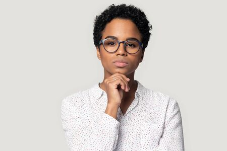 Thoughtful young african american female professional looking at camera, head shot close up portrait. Pensive concentrated ethnic girl in eyeglasses touching chin, isolated on grey studio background. Stock fotó