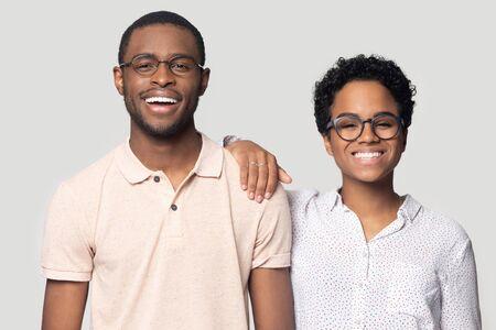 Lächelndes aufgeregtes afroamerikanisches verheiratetes Familienpaar in Brillen mit Blick auf die Kamera. Junge glückliche schwarze Frau, die sich auf die Schulter des Mannes stützt und für Foto posiert, isoliert auf grauem Studiohintergrund. Standard-Bild