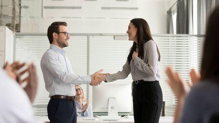 Glimlachende duizendjarige mannelijke baas handdruk opgewonden verrast vrouwelijke werknemer begroeting met promotie of werkgelegenheid, zakenman schud de hand van gelukkige vrouwelijke werknemer feliciteren, collega's applaudisseren
