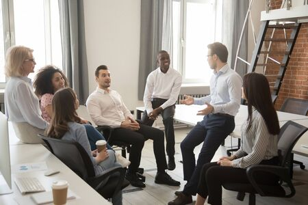 Multiethnic work group talk during casual office meeting, discuss business ideas sharing thoughts, smiling diverse colleagues or employees speak negotiating at informal briefing at workplace