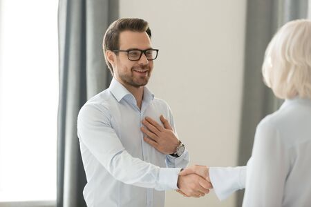 Smiling millennial businessman handshake woman partner or colleague get acquainted at first meeting, male employee shake hand of female coworker happy to introduce or greeting with promotion