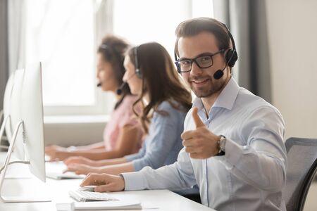 Il dipendente maschio sorridente che indossa l'auricolare si siede alla scrivania dell'ufficio condivisa che lavora al pc mostra pollice in su, l'agente del call center lavoratore millenario felice consiglia il servizio, consulta i clienti sul computer online Archivio Fotografico