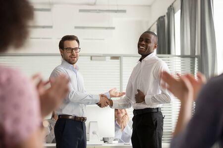 Millennial businessman shake hand of happy african American worker talk congratulate with business success, happy male team leader or boss handshake black employee greeting with promotion Foto de archivo