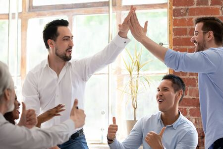 Multi-racial colleagues staff share success showing thumbs up cheering looking at two leaders Middle Eastern and European appearance colleagues giving high five, cooperation unity and support concept