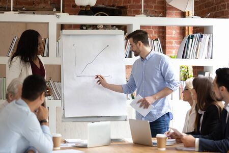 Diverse corporate staff sitting at desk take part in business training at boardroom listens look at handwritten carts graphs on flip chart, business coach teach members lead corporate lecture concept