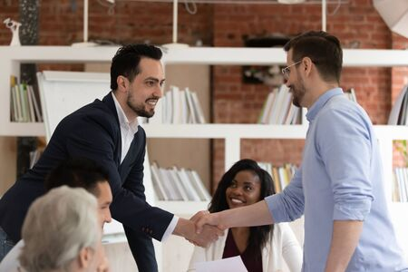 Satisfied diverse employees take part at meeting, middle east appearance and european businessmen shaking hands. Concept of partnership and business people reached agreement acceptable to both parties