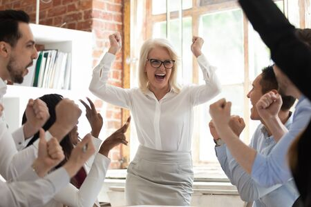 Excited happy diverse staff in spotlight overjoyed middle-aged woman team leader screaming with joy, department celebrating business success make great deal, fantastic results, growth of sales concept