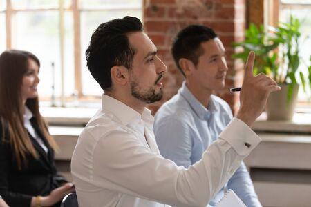 Personas multiétnicas participan en el seminario, la vista lateral se centra en el hombre del Medio Oriente levantando la mano para hacer preguntas en la capacitación corporativa para expresar una opinión personal sobre el tema, concepto de conferencia educativa