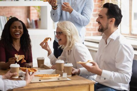Multi-ethnic workers sit at desk laughing have fun eat pizza drink tea or coffee enjoy conversation joking take break during working day, food delivery service, team building, corporate party concept Archivio Fotografico