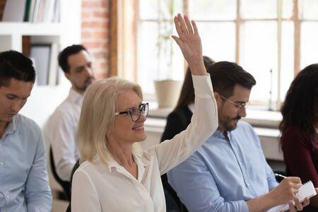 Diverses personnes participent à une conférence ou à un séminaire assis sur des chaises dans une salle de bureau, l'accent sur une femme d'âge moyen lève la main pour poser une question participant actif à la formation, concept d'éducation en entreprise Banque d'images
