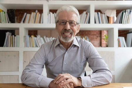 Positive aged grey-haired businessman in glasses sit at desk looking at camera, webcam view. Portrait of skilled financial advisor lead online course old entrepreneur and virtual communication concept Reklamní fotografie