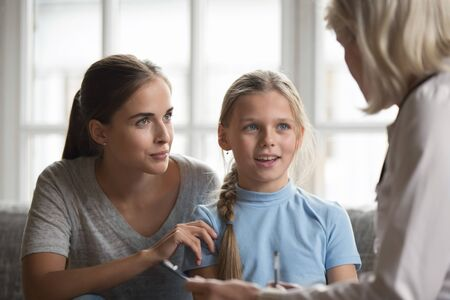 Young mother and little daughter visit female doctor talk about health complains, woman pediatrician consult girl with mom, make notes in card, write medicine prescription, children healthcare concept