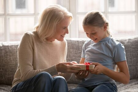 Liebevolle Großmutter mittleren Alters 60 sitzt auf der Couch Gruß gratuliert der kleinen Enkelin zum Geburtstag, fürsorgliche Senior-Oma macht Überraschungsgeschenk verpackte Geschenkbox mit roter Schleife für überraschten Nachwuchs Standard-Bild