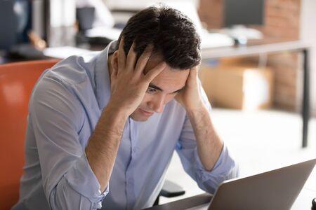 El hombre de negocios sentado en el escritorio hace que los ojos grandes sostengan la cabeza con las manos mirar la pantalla de la PC se siente estresado por tener problemas, mal funcionamiento del software, pérdida de datos importantes, mensaje incorrecto recibido, concepto despedido