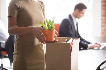 African woman new employee standing in shared open space holding flower pot unpacking belongings with personal stuff having first working day. Employment headhunting labour, promotion at work concept Banque d'images