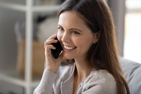 Primer plano de una sonriente adolescente positiva hablar en un teléfono inteligente que tiene una conversación agradable con un amigo, una mujer joven feliz que sostiene un teléfono celular que habla y que se comunica, usa una conexión inalámbrica o 5g
