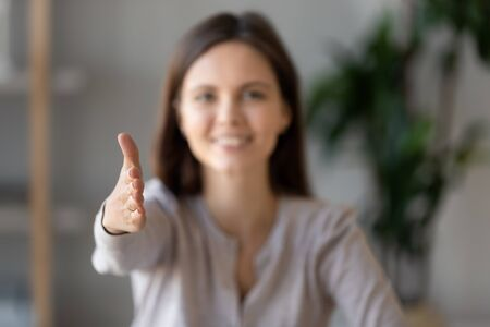 Focus close up of smiling young female employer stretch hand greeting potential job candidate at hiring meeting, happy woman boss shake hand introducing welcome applicant at interview in office