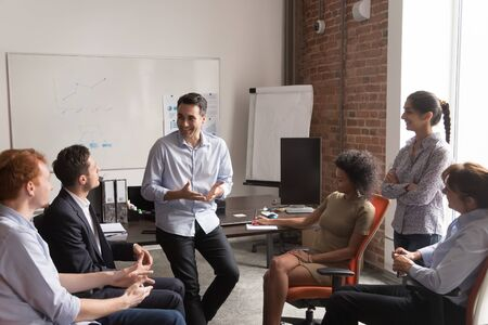 Multi racial businesspeople gather at briefing, positive team leader talking to office employees interns or students at corporate training teach explain project strategy discuss business plan concept