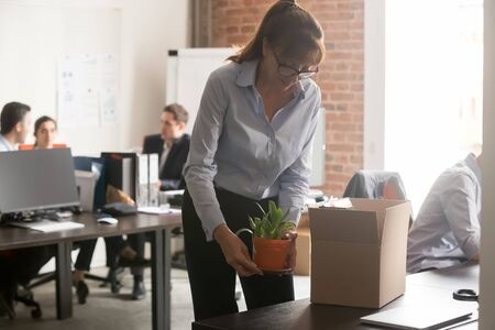 Satisfied newcomer middle aged female company worker in glasses standing in shared coworking office unpacking cardboard box with personal belongings at new workplace having first working day concept Banque d'images