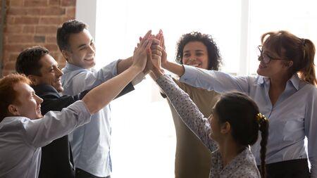 Les hommes d'affaires multiraciaux ravis réussissent leur objectif en donnant un high five se sent excité. Une équipe d'entreprise réussie se félicitant de la victoire se tient la main ensemble montre l'esprit d'unité