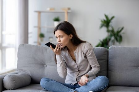 Angry young woman sit on couch having unpleasant cellphone talk scream at mobile, mad furious girl feel emotional hold cell yell speaking on smartphone, millennial female dispute explaining something