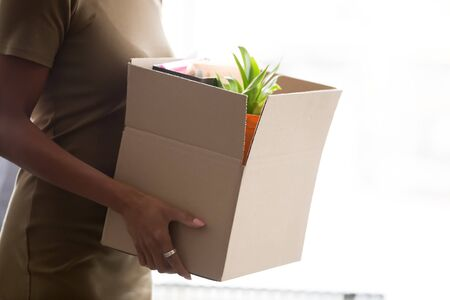 Cropped close up image mixed race female hands holding cardboard box with belongings stuff new employee member starting career in company having first working day. Newcomer hiring employment concept Stock Photo
