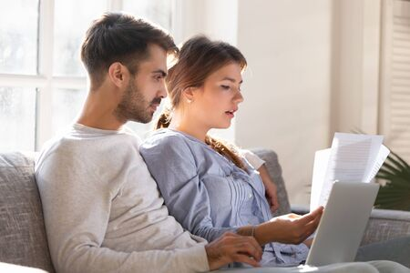 Focused young couple checking bills, reading bank loan documents with laptop together, sitting on couch, wife and husband planning budget, managing finances, using internet banking service