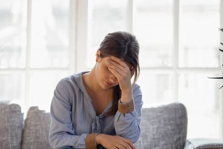 Upset young woman hiding face in hand, crying, thinking about problem, sitting alone on couch at home, girl feeling unhappy, breakup, need psychological help, offended abused, addiction trouble