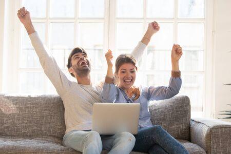 Feliz pareja joven celebra la victoria en línea, gritando de alegría levantando las manos, mirando juntos la pantalla del portátil, esposa y esposo reciben buenas noticias, logros, nuevas oportunidades de gran oferta, éxito