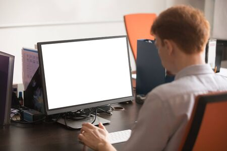 Rear side over shoulder view redhead businessman company employee sitting in workplace working use computer with mock up white blank screen, empty copy space on monitor for your business advertisement