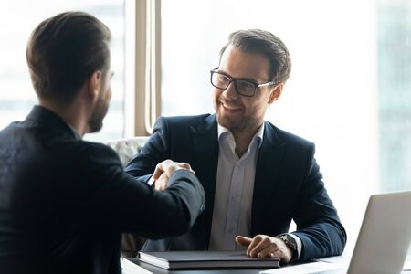 Happy male business partners shake hands greeting get acquainted at meeting in office, smiling businessmen handshake close deal make agreement at briefing, partnership, cooperation concept Stock Photo