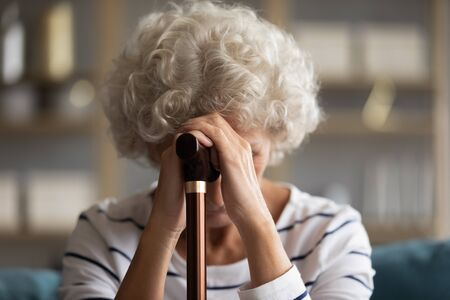 Close up view sad 60s woman bowed her head hiding face with hands holding walking cane stick, aggrieved about illness physical damage, chronic progressive movement disorder Parkinson disease concept
