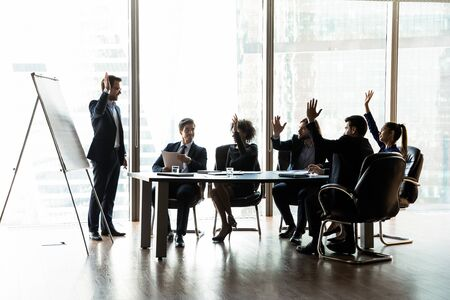 Male coach lead meeting with multiracial colleagues make flip chart presentation interact with coworkers at briefing, multiethnic businesspeople participate in teambuilding activity at meeting Stock Photo