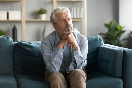 Pensive 50s man seated on couch lost in sad thoughts looks to nowhere feels abandoned and lonely. Concept of dementia illness of old generation people, mental disorder, difficult life unhappy person