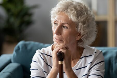Close up 70s upset grandmothers face lonely disabled woman sit on sofa holding stick cane looking away feeling loneliness and solitude she has physical damage as result of accident or illness concept