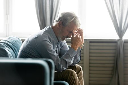 Side view in living room seated on couch hunched old 50s male hold hands near face looking desperate and lonely feels worried. Concept of illness and diagnosis, older generation humans life troubles