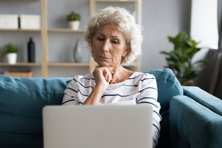 Old woman sit on couch looks at laptop screen feels confused, difficulties with modern gadgets, not understanding how it works, need assistance in learning to use devices and digital services concept
