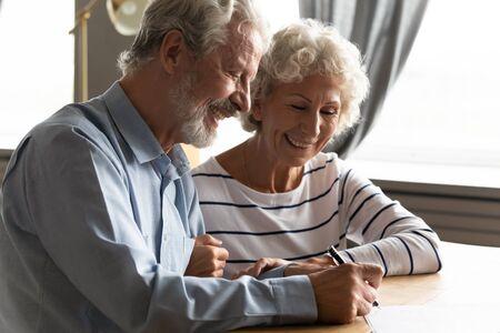 Un couple de personnes âgées satisfait au bureau d'un avocat signant des articles sur le mariage d'un accord prénuptial, les conjoints des années 70 prennent la décision d'acheter une assurance-maladie médicale, le concept de testament et d'héritage