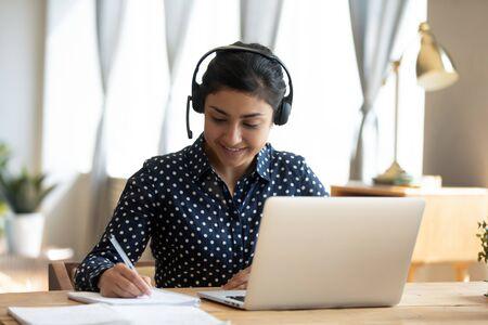 Fröhliche indische Studentin trägt Headset-Studie online mit Webcam-Lehrer, schreibt Notizen, glückliche junge Frau hört Vorlesungswebinar auf Laptop am Schreibtisch sitzen, Fernunterricht und Sprachbildungskonzept lernen