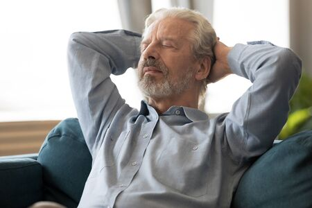 Close up view senior man enjoy day off leaned on couch put hands behind head posture of relaxation or meditation feeling calmness and serenity enjoy retired life and pleasant solitude indoors concept