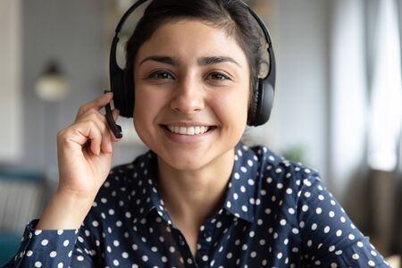 Uśmiechnięta indyjska dziewczyna nauczyciel doradca agent telesprzedaży nosić bezprzewodowy zestaw słuchawkowy patrzeć na kamerę internetową, nauczanie na odległość, koncepcja obsługi klienta, telemarketing profesjonalny portret zbliżenie