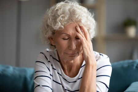 60s woman closed eyes touch forehead suffers from migraine feel discomfort caused by high blood pressure, worried disappointed grandmother having life personal or health problem concept close up image Imagens