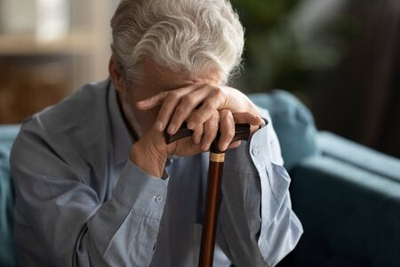 Close up sad 70s elderly man covering his face with hand holding walking stick looking desperate and lonely goes through rehabilitation, chronic progressive Parkinson disease movement disorder concept