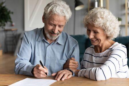 Cónyuges ancianos de los años 60 en la oficina del abogado sentados en el escritorio marido canoso con bolígrafo firmar el contrato matrimonial listo para la familia hacen formalidades legales en notario, legar ahorros y bienes a los hijos concepto