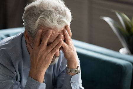 50s man hides his face with hands looking desperate close up, aged male sit on couch at home thinking search decision feels unwell, mental disorders of older people, senile diseases, dementia concept Stock Photo