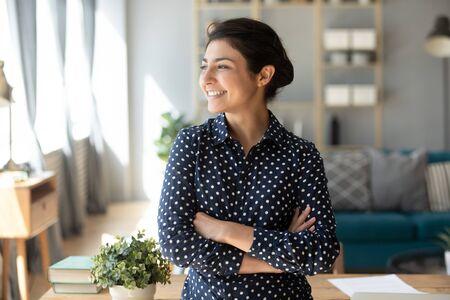 Feliz satisfecho joven indio estudiante profesor freelance apartar la mirada soñar con una buena visión de futuro, sonriente chica guapa profesional soporte con los brazos cruzados en casa esperanza de nuevas oportunidades concepto